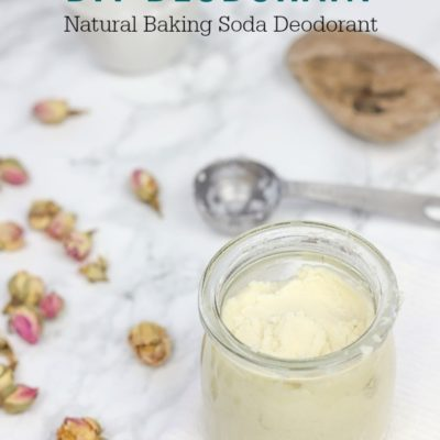 DIY deodorant in a glass jar on a white wash cloth with rose buds to the left and a steel measuring spoon behind it.