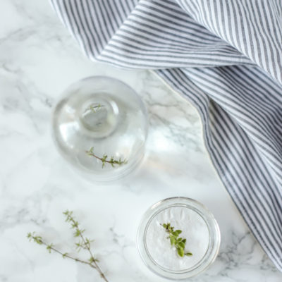 two ingredients to make drain cleaner in glass jars on a marble countertop with fresh herbs
