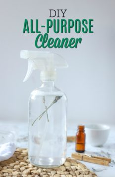 glass spray bottle of DIY all-purpose cleaner on a rattan place mat and ingredients around it
