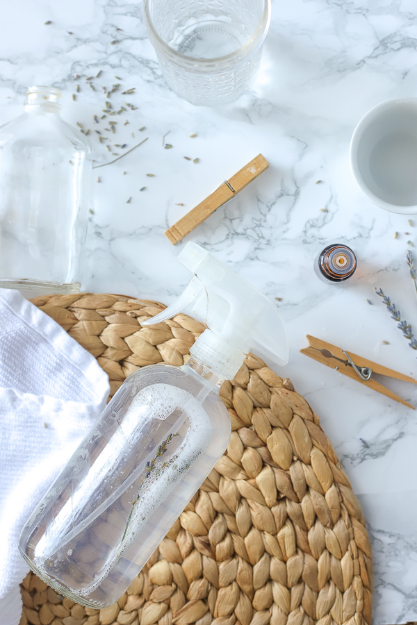 DIY All-Purpose cleaner on a rattan place mat with clothes pins and essential oils around it