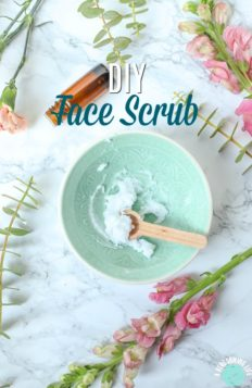teal bowl of DIY face scrub with a wooden spoon and flowers all around.