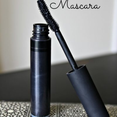 tube of natural homemade mascara on a black and white patterned plate