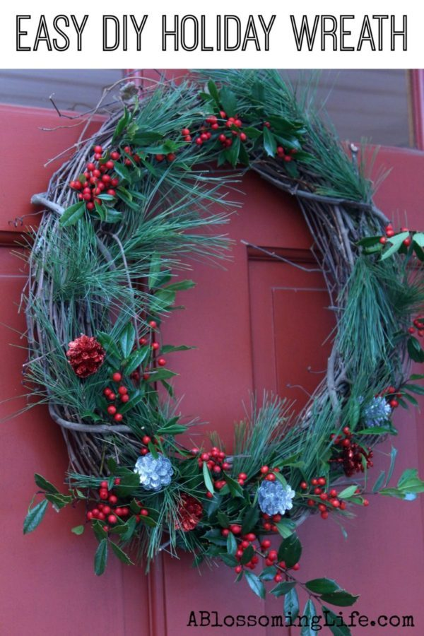 DIY Christmas Wreath with greenery, holly, and pinecones hanging on a red door