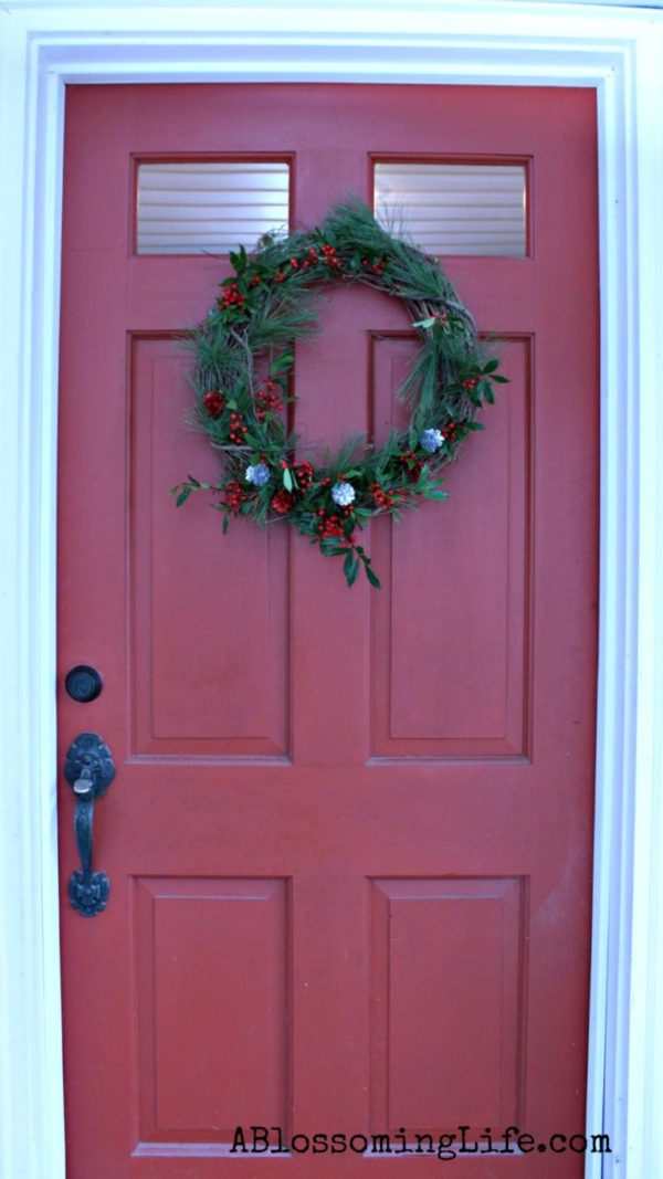 Red door with DIY Christmas wreath with greenery, holly, and pinecones