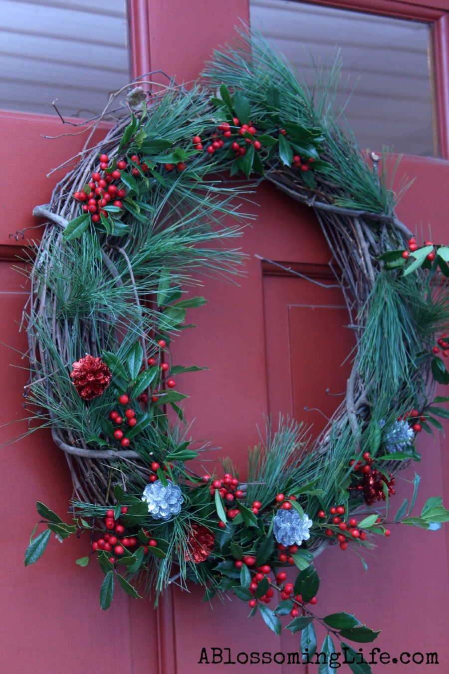 DIY Christmas Wreath with evergreens, holly, and sparkly pinecones hanging on a red door.