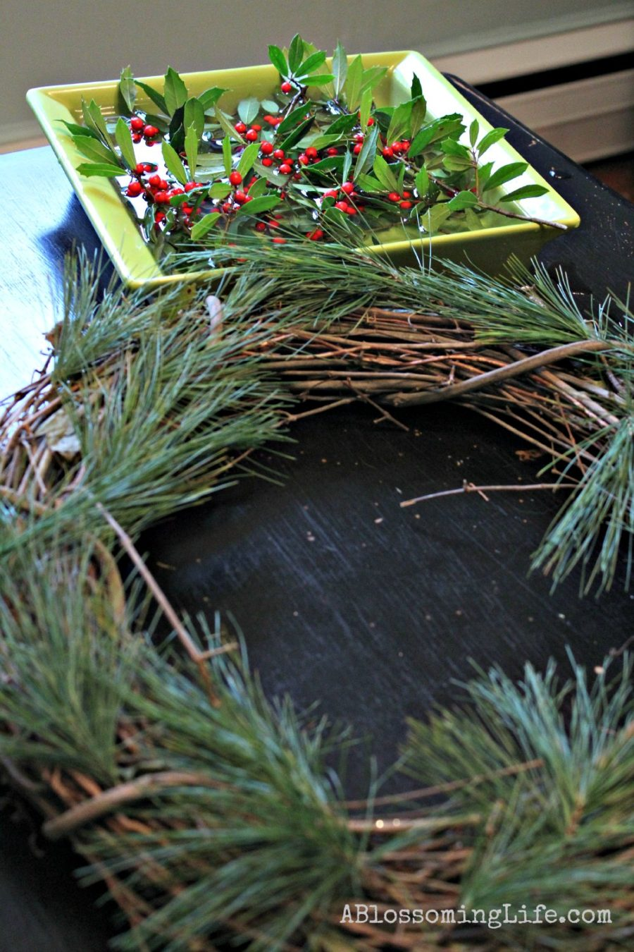 Twig wreath with evergreens attached and holly soaking in water behind it to make a DIY Christmas Wreath