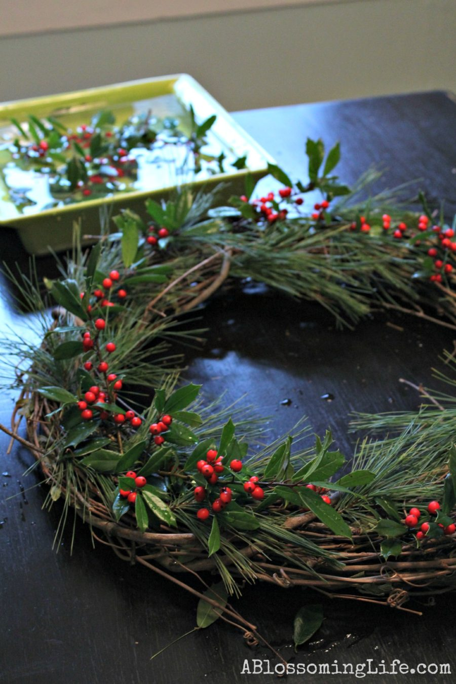 Placing holly in a twig wreath with evergreens to create a DIY Christmas Wreath