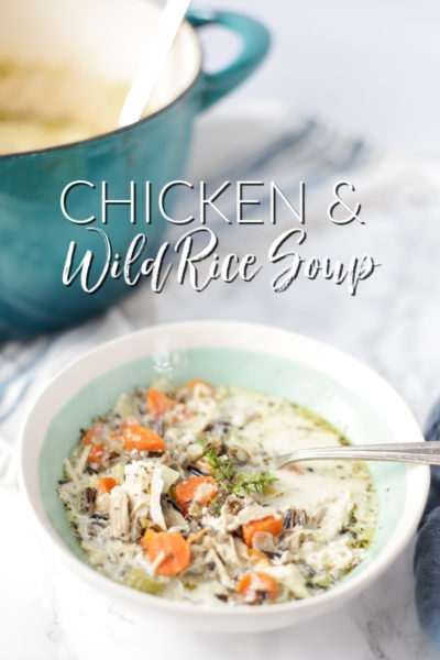 creamy chicken and wild rice soup with carrots, celery, chicken, wild rice and onions in a creamy base and topped with fresh herbs in a cream and teal bowl with a dutch oven behind