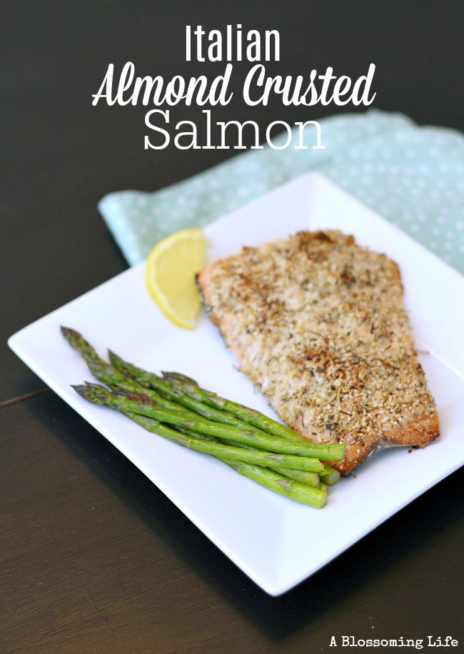 Italian almond crusted salmon on a white plate with asparagus and lemon slice