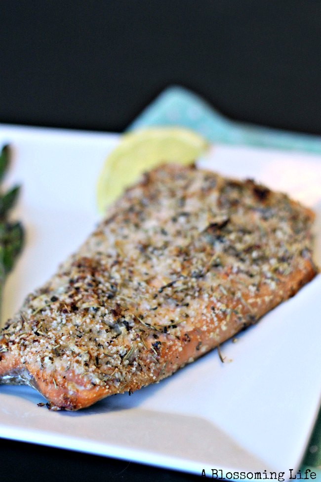 Italian crusted salmon on a white dish with lemon slice