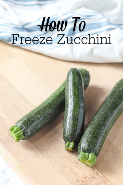 three fresh zucchini laying on a wood cutting board with a blue and white striped napkin behind it