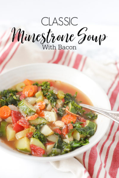 bowl of classic minestrone soup with bacon in a white bowl with a red and tan stripped towel
