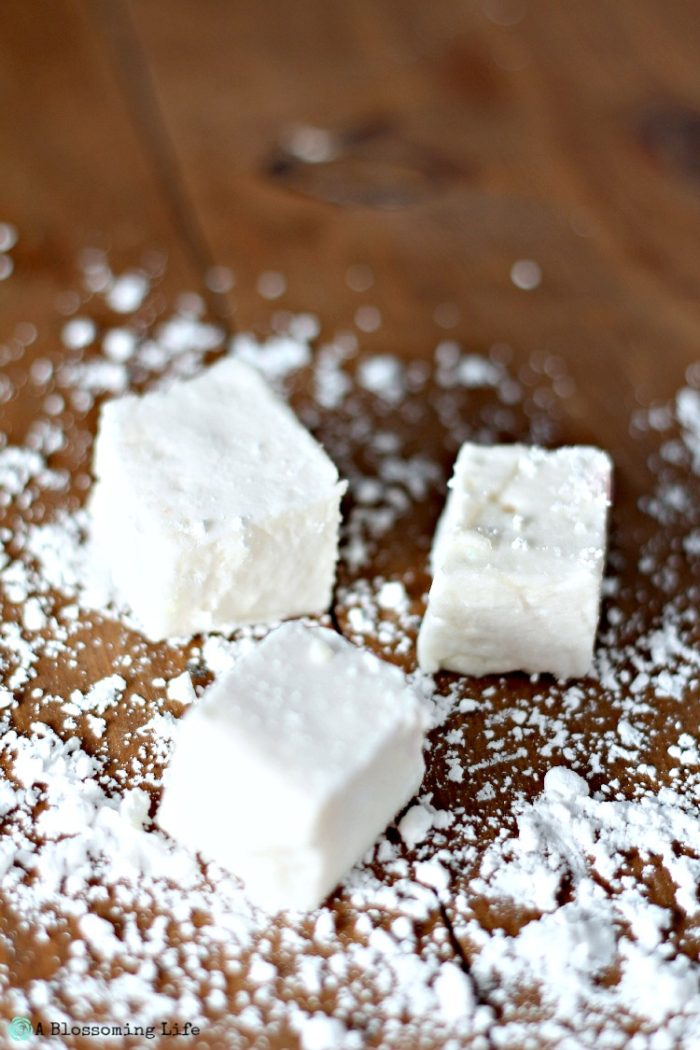 three homemade marshmallows on a wood table with cornstarch sprinkled around