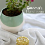 DIY sugar scrub in a small glass jar on top of a white towel with a flowering plant in the background
