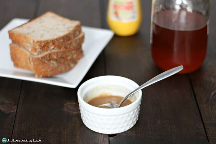 homemade honey mustard in a white dish with bread , honey, and mustard in the background