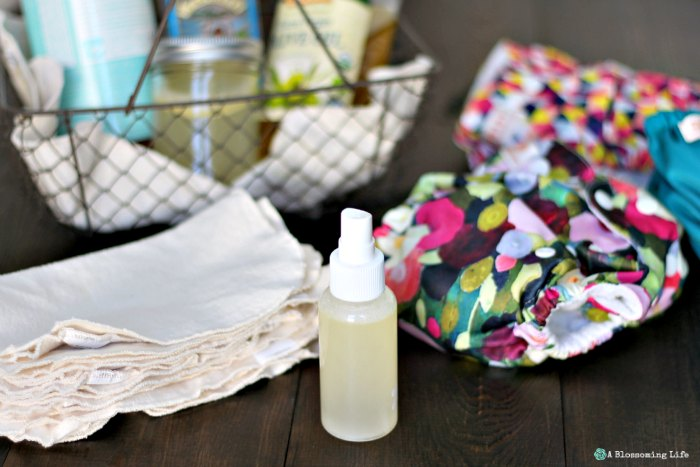 homemade baby wipe solution in a spray bottle with reusable wipes to the left and cloth diapers to the right
