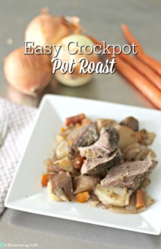 Pot Roast, carrots, and potatoes made in a slow cooker on a white plate with with carrots and onions behind it