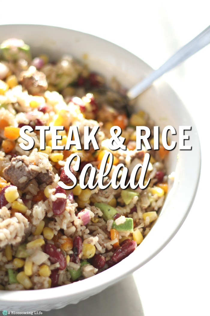 Steak rice salad in a white bowl with a spoon coming out