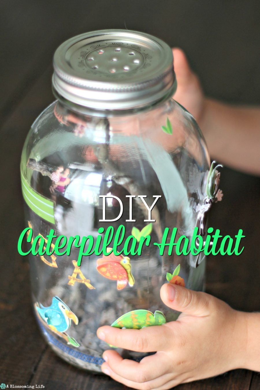 kid hands holding a DIY Caterpillar Habitat made from a mason jar and covered with stickers
