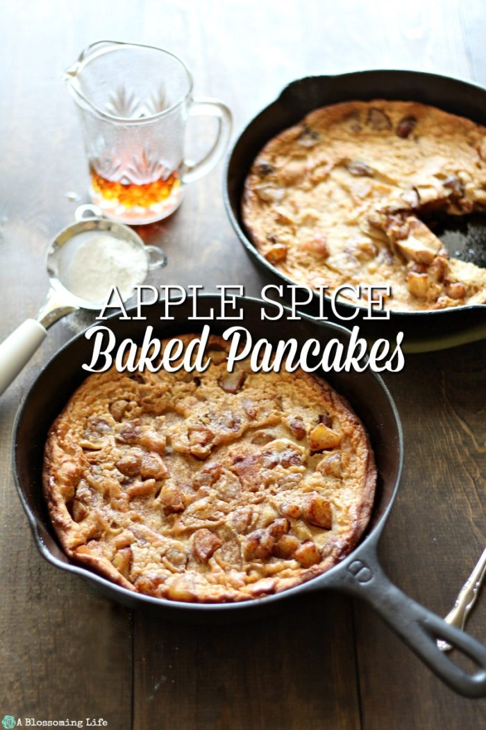 Two bakes Pancakes with spiced apples in cast iron skillets with maple syrup and powder sugar behind it.