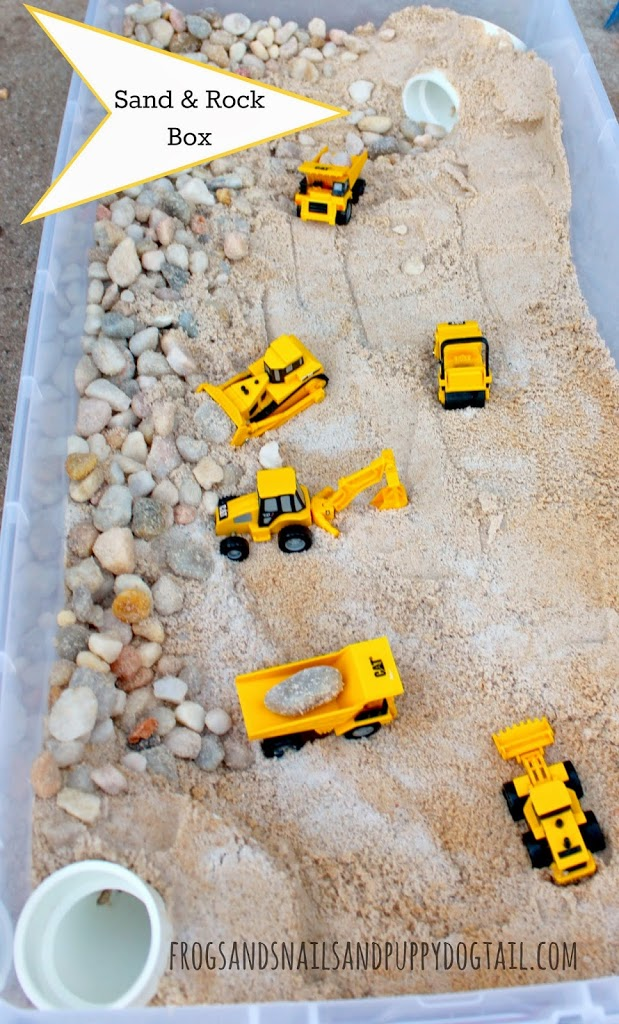 a plastic box with sand, rocks, and toy trucks for a fun fall activities for preschoolers