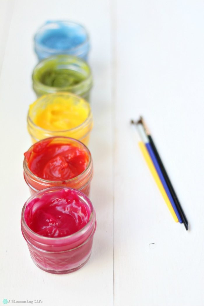 homemade finger paints in glass jars with paint brushes to the side