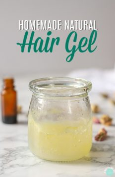 glass jar of homemade natural hair gel with essential oils and rose buds behind it