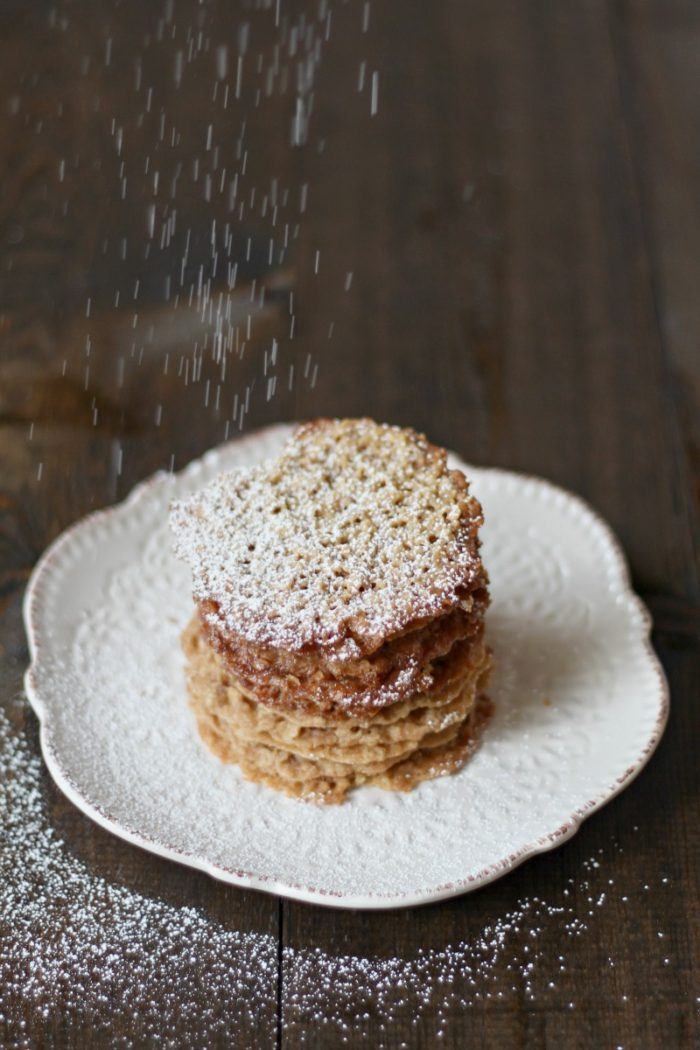 Lace Cookies stacked on a cream colored dish being sprinkled with powdered sugar