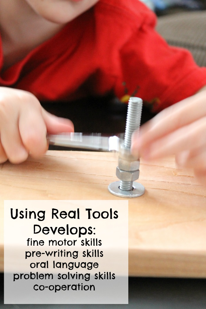 child with a red shirt using a wrench on nuts and bolts on a piece of wood.