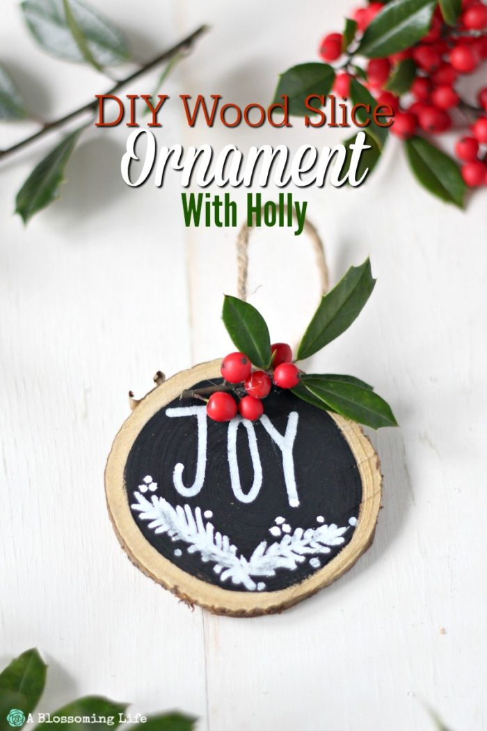 Wood Ornaments with holly and twine on a white board with holy behind it