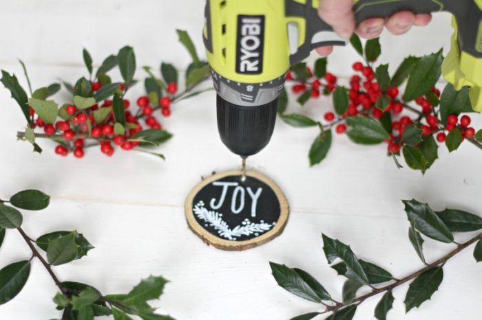 wooden ornament with the center pud black and white letters spelling JOY with white stems painted below. Drill putting a whole in the upper middle potion and holly surrounding the boarder of the picture.