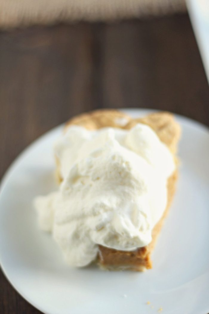 slice of pumpkin pie covered in whipped cream on a white plate