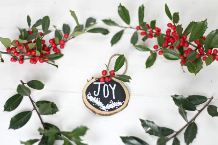 wooden ornament with black painted int he middle, JOY written in white paint with a garland drawing below, twine tied through the hole and holy glued on top.