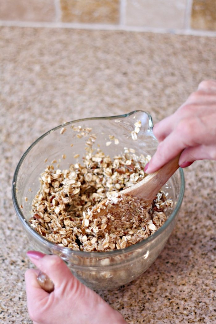 mixing granola in a glass bowl on a granite counter