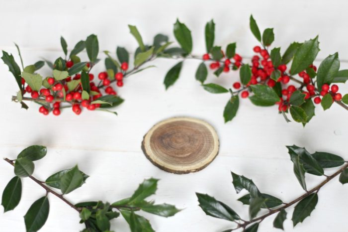 wood slice on a white board surrounded by holly to begin making a wooden ornament.