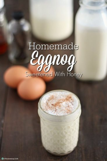 homemade eggnog in a glass mason jar with eggs, vanilla extract, cream, and a jar of eggnog in the background.