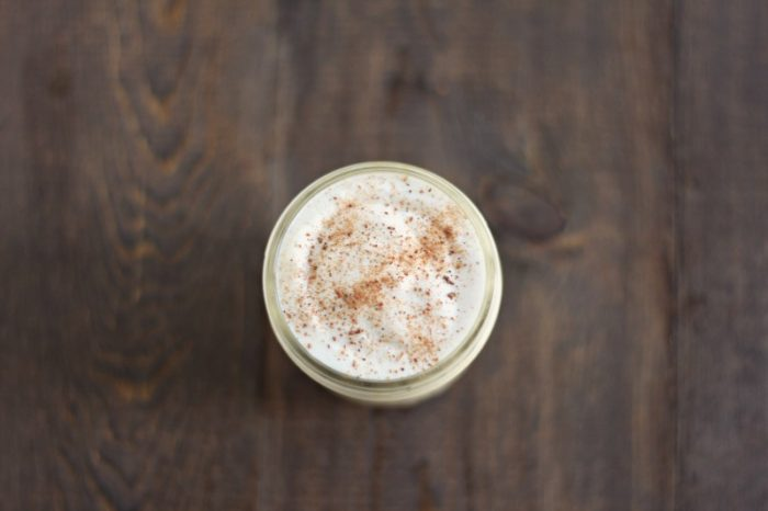 top view of homemade eggnog in a mason jar and topped with nutmeg