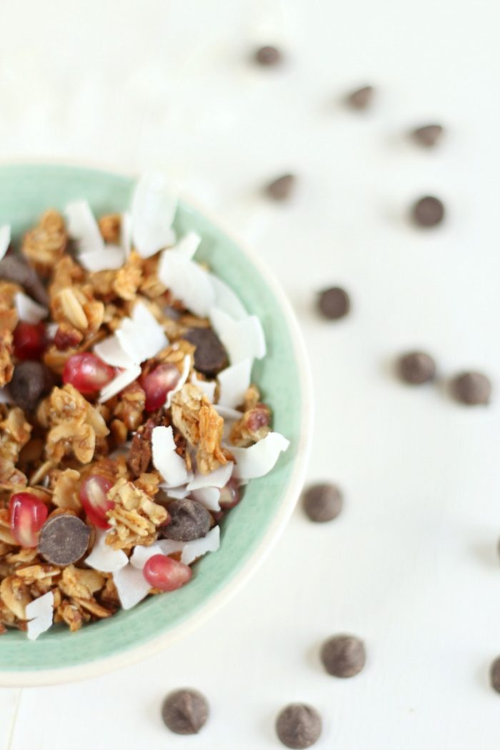 half teal bowl filled with homemade granola, chocolate chips, pomegranate seeds, and coconut shavings with chocolate chips scattered around the bowl