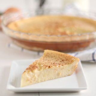 slice of custard pie on a white dish with the whole pie behind it on a white and blue towel