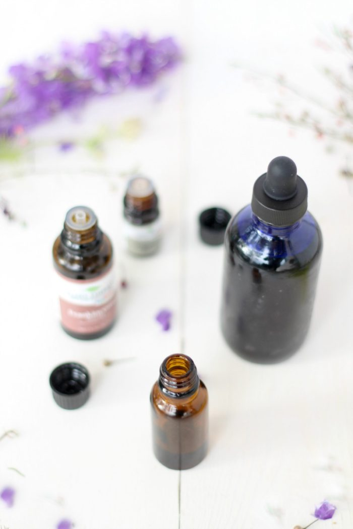 amber bottle of face serum with a blue bottle, essential oils, and purple flowers behind it.