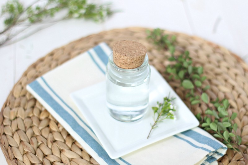 diy mouthwash in a glass jar on a white plate and rattan mat