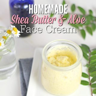 Shea butter cream sitting on a white place on a blue napkin with leaves and flowers in a jar behind it.
