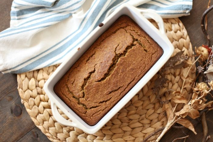 overhead shot freshly baked loaf of gluten free pumpkin bread in a ceramic bread pan on a rattan place mat with a blue and cream stripped towel behind it