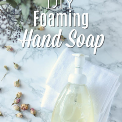 Foaming hand soap on a white wash clothes with eucalyptus leaves and dried roses to the left