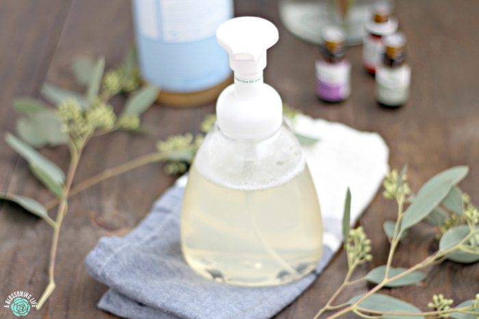 foaming hand soap in a bottle on a blue napkin with eucalyptus on each side and essential oils behind it.