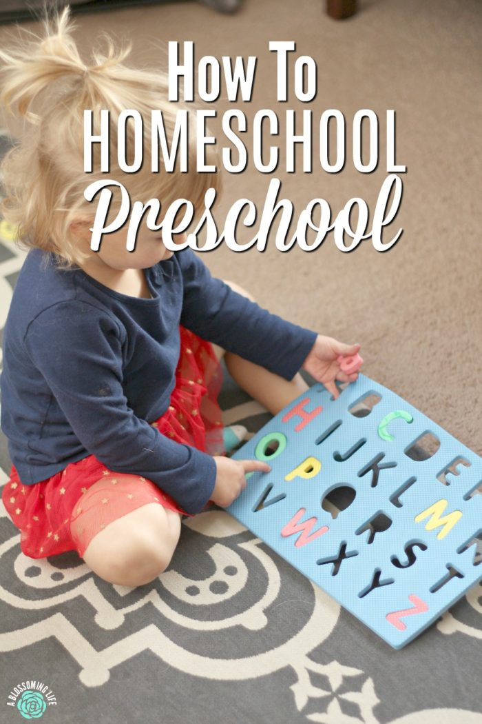Child playing with letter mat for homeschool preschool lesson