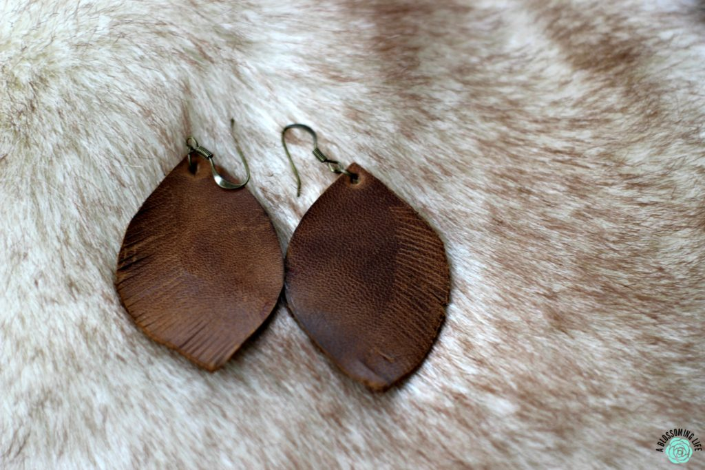 pair of brown DIY leather earrings laying on faux fur