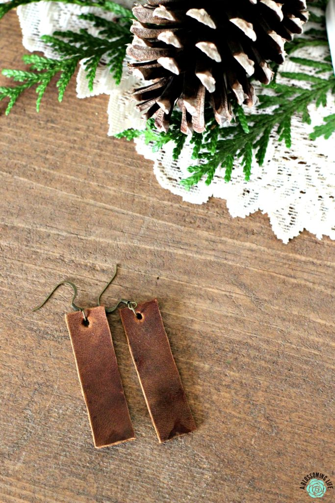 Pair of brown rectangular earrings laying on a table with pine cones on a while fabric doily behind it