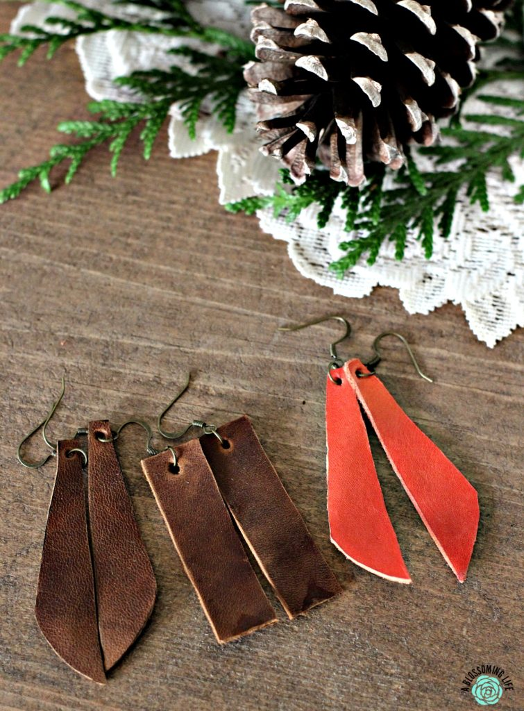 3 pairs of DIY leather earrings on a table with pine cone behind it