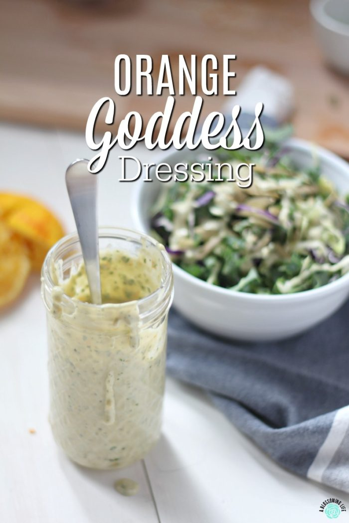Orange Goddess Dressing in a glass jar with a kale salad behind it